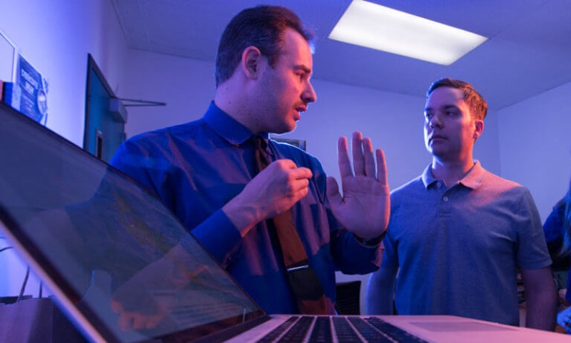 A photo of Mikhail Gofman, left, associate professor of computer science and director of CSUF's Center for Cybersecurity, mentoring a student.
